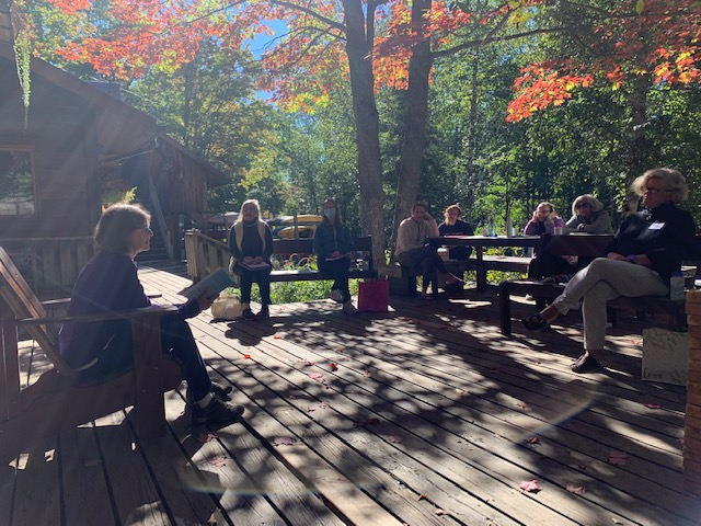 A woman sitting on a wood deck is reading from her work on a beautiful fall day to a group of women